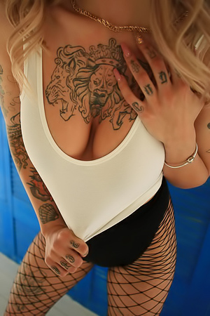 Glamour busty blond with tattoo