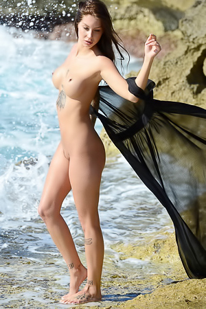 Naughty Lena showing her nude tattooed body on a rocky beach